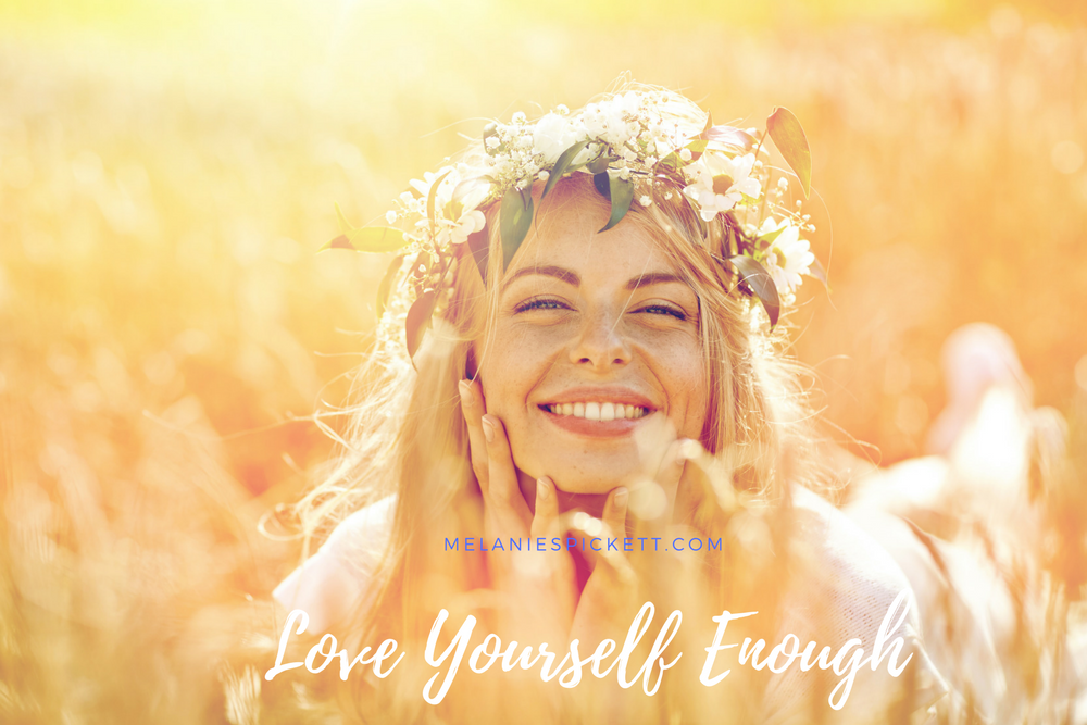 love yourself enough. woman smiling in meadow of flowers